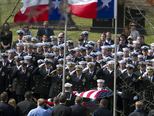 "Military personnel salute the casket of former Navy SEAL Chris Kyle in Austin on Feb. 12. Kyle, author of ""American Sniper,"" and a friend were killed at a shooting range. Police have arrested Eddie Ray Routh, a veteran of the Iraq War. (Photo: Deborah Cannon, AP)"
